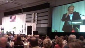 Ambassador Tony Hall gestures on the video screen during the 25th annual Colorado Prayer Luncheon. (Marrton Dormish)
