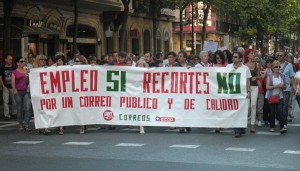 """Protesters line the street in Donostia, Spain, on July 19. The large banner they are holding reads, """"Employment Yes (Budget) Cuts No."""" (Joxemai via Wikimedia Commons)"""
