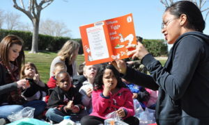 Taimane Mejia, a volunteer at McTureous Hall aboard Marine Corps Logistics Base Barstow, reads to children from the Child Development Center for the annual Dr. Seuss Birthday Bash, March 2, 2012. During the event, children had stories read to them to help stress the importance of literacy at all ages and participated in other activities such as coloring and games. (United States Marine Corp via Wikimedia Commons)