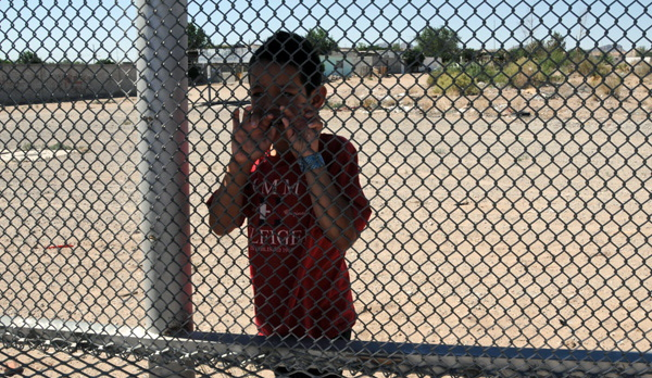 Nine-year-old Luis standing on the Mexican side of the border at Anapra, and talking through the fence with me and a friend. (Photo by Heath Haussamen)