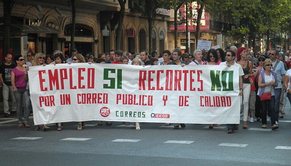 "Protesters line the street in Donostia, Spain, on July 19. The large banner they are holding reads, ""Employment Yes (Budget) Cuts No."" (Joxemai via Wikimedia Commons)"