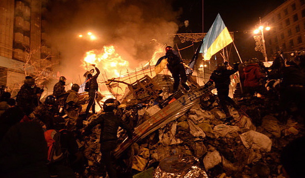 The state flag of Ukraine is carried by a protester to the heart of developing clashes in Kyiv, Ukraine, on Feb. 18, 2014 (Mstyslav Chernov via Wikimedia Commons)