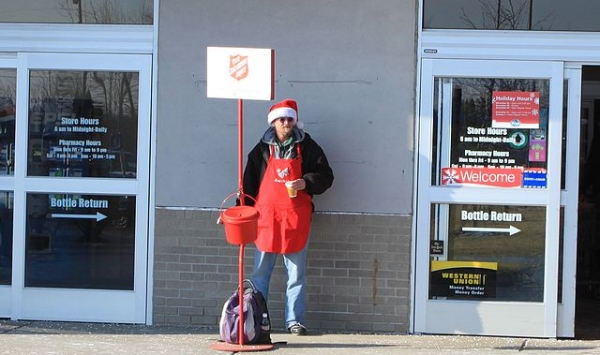 A Salvation Army red kettle and bell ringer outside a Kroger supermarket in Ypsilanti, Michigan.(Dwight Burdette via Wikimedia Commons)
